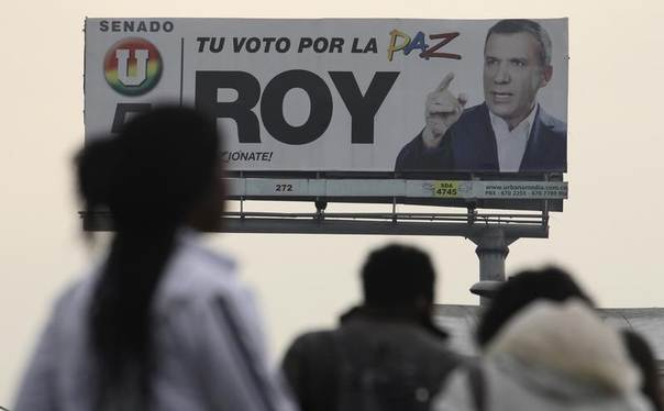 People walk in front of a billboard of legislative candidate Roy Barreras of the National Unity or
