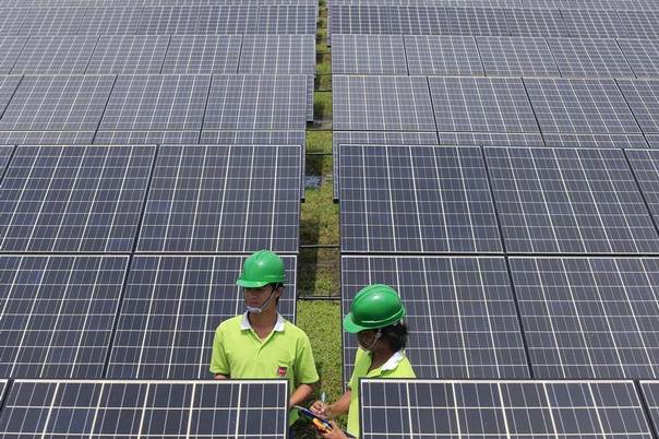 Two employees of SPCG, Thailand's largest solar farm producer, take notes between panels in Korat, Nakorn Ratchasima province, October 3, 2013. REUTERS/Athit Perawongmetha