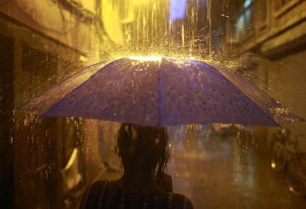 A woman holding an umbrella walks on flooded streets during heavy rainfall in Kathmandu, Nepal, May 23, 2013. REUTERS/Navesh Chitrakar
