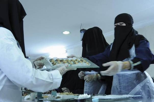 Veil-clad female workers work at a factory for pickling olives, dates, jam productions and olive oil in the Saudi city of Tabuk August 22, 2013. REUTERS/Mohamed Al Hwaity
