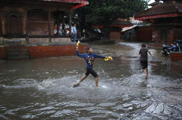 A boy throws a flip-flop towards his friend as they play on the waterlogged streets of Bashantapur Durbar Square, during a rain in Kathmandu June 24, 2013. REUTERS/Navesh Chitrakar