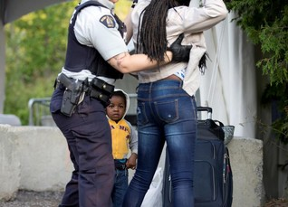 Two-year-old Evanston, whose family stated they are from Haiti, watches as a Royal Canadian Mounted Police (RCMP) officer pats down his mother after they crossed the US-Canada border from Champlain, New York into Lacolle, Canada August 11, 2017