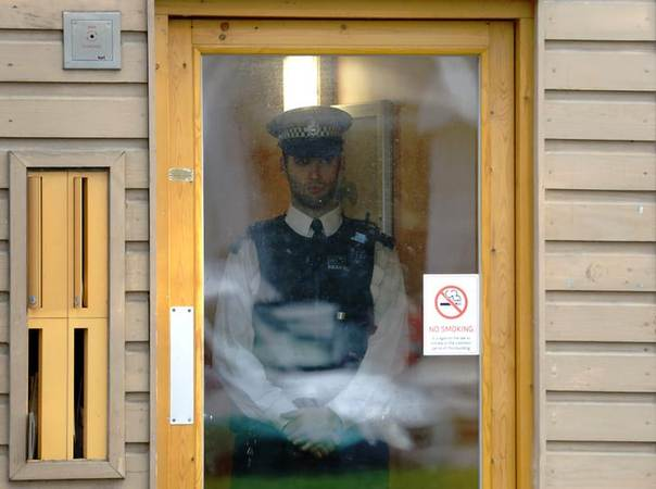 Police stand guard at a property in Lambeth, south London November 23, 2013. REUTERS/Luke MacGregor
