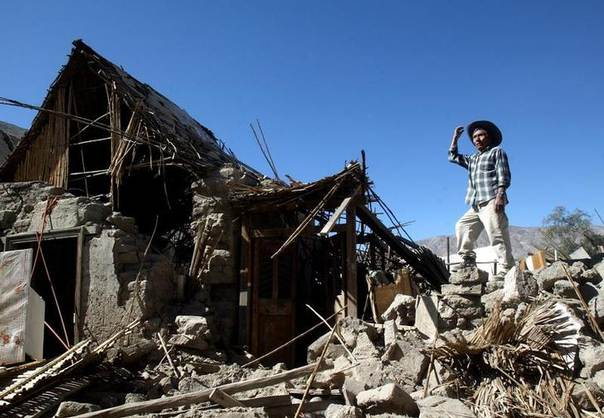 Ernesto Mamani stands over his destroyed house in Tarapaca town off Iquique, about 1845km (1146 miles) north of Santiago, Chile June 15, 2005. REUTERS/Ivan Alvarado IA/PN