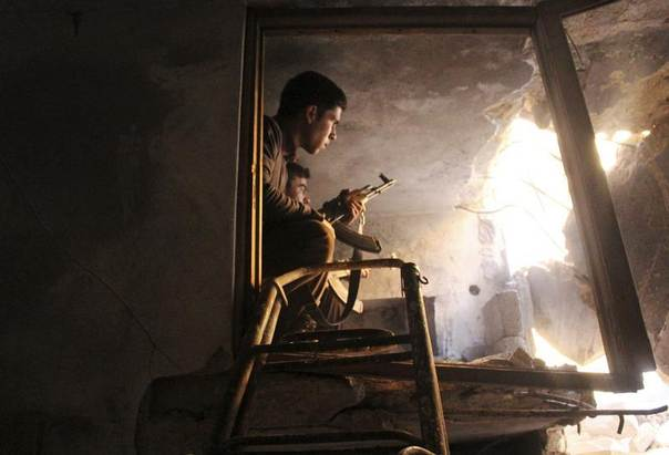 Free Syrian Army fighters sit in a damaged house with their weapons in Old Aleppo, Syria, December 21, 2013. REUTERS/Abdalrhman Ismail