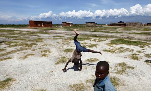 A child does a cartwheel in Gatumba, outside Bujumbura, as clouds shroud the mountains of eastern Democratic Republic of Congo April 19, 2013. REUTERS/Darrin Zammit Lupi