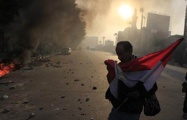 Anti-government protester holds a national flag during clashes at Ramsis street, which leads to Tahrir Square in downtown Cairo, on the third anniversary of Egypt's uprising, January 25, 2014. REUTERS/Amr Abdallah Dalsh
