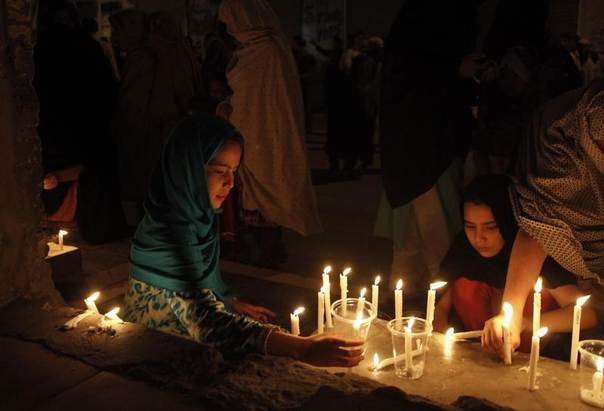 Shi'ite Muslims girls light candles with others to mourn the victims of a suicide attack at a hotel in Taftan, located near the Iranian border, in Quetta, Pakistan, June 10, 2014. REUTERS/Naseer Ahmed