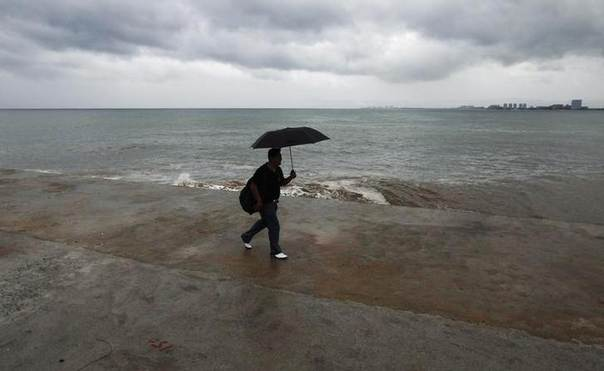 A man holding an umbrella walks along the boardwalk in Puerto Vallarta October 12, 2011. REUTERS/Carlos Jasso
