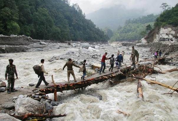 Indian army personnel help stranded people cross a flooded river after heavy rains in the Himalayan state of Uttarakhand June 23, 2013. REUTERS/Stringer