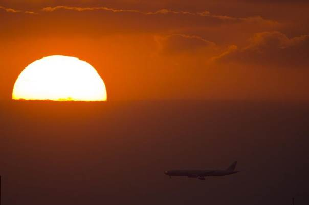A passenger jet flies past the setting sun in Shanghai, Sept. 17, 2013. REUTERS/Aly Song