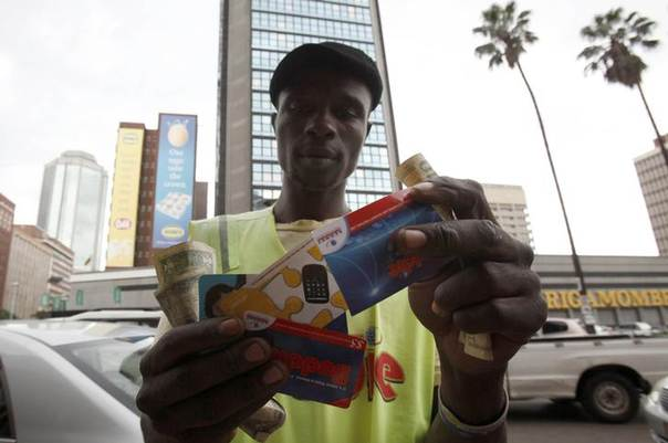 Qualified carpenter Alex Mhazo sells mobile phone cards in central Harare, in this picture taken April 1, 2014. REUTERS/Philimon Bulawayo