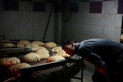 A man inspects a line of bread to be distributed as aid in Syria