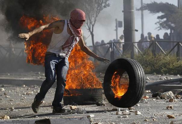 A Palestinian stone-thrower stands next to a tyre set ablaze during clashes with Israeli police in Shuafat, an Arab suburb of Jerusalem, July 3, 2014. REUTERS/Ammar Awad