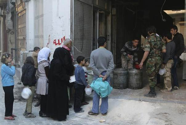 Civilians queue to receive free food distributed by Free Syrian Army fighters to the residents living near the frontline in the old city of Aleppo March 31, 2014. REUTERS/Mahmoud Hebbo