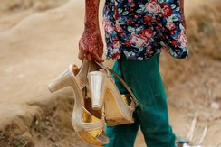 A Bangladeshi girl carries her older sister's golden shoes as their family visits Rohingya refugee camp Balukhali near Cox's Bazar