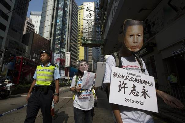 A pro-democracy protester, wearing a mask depicting a Chinese political prisoner, carries a placard with the prisoner's name and his charges, during a protest calling for the release of political prisoners in Hong Kong October 1, 2013. The placard reads,