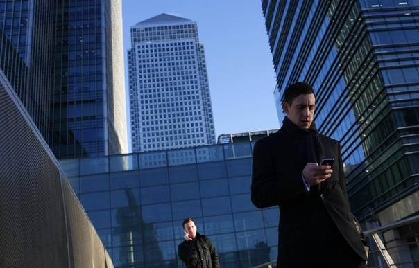 A worker looks at his phone at the Canary Wharf business and financial district in London February 26, 2014, REUTERS/Eddie Keogh