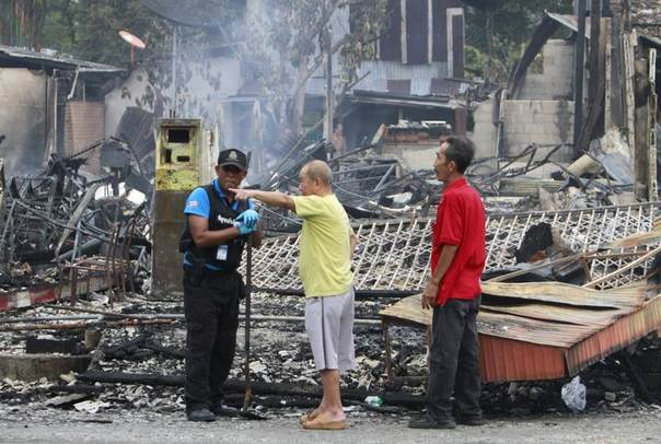A Thai security personnel speaks with villagers at the site of a bomb attack, in the southern Narathiwat province, Thailand, May 12, 2014. REUTERS/Surapan Boonthanom