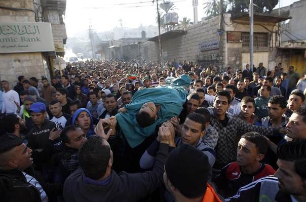 Palestinians shout slogans as they carry the body of Palestinian Yazan Jabarin in the West Bank refugee camp of Jenin March 22, 2014. REUTERS/Mohamad Torokman