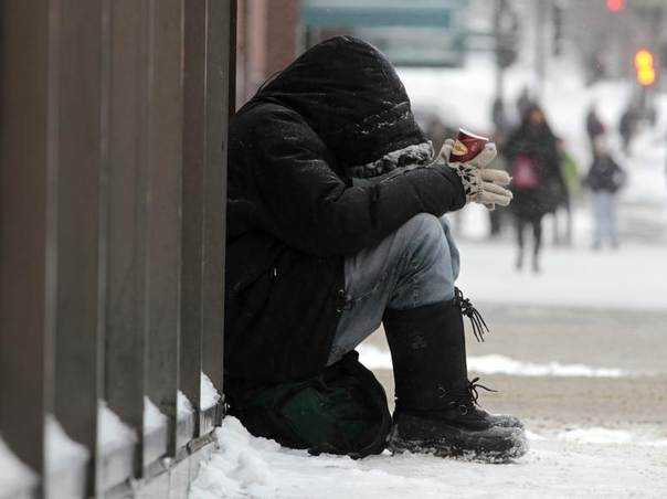 A man begs for money on Sainte Catherine Street on a cold winter day in Montreal, February 8, 2011. REUTERS/Shaun Best
