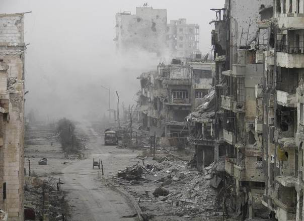 Smoke rises from buildings after what activists said was shelling from forces loyal to Syria's President Bashar al-Assad in the besieged area of Homs, Syria, January 15, 2014. REUTERS/Thaer Al Khalidiya