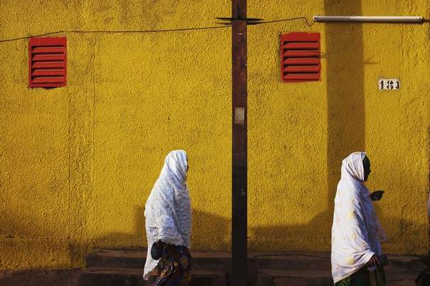 Women walk past the yellow exterior of a supermarket in Niamey, September 19, 2013. REUTERS/Joe Penney
