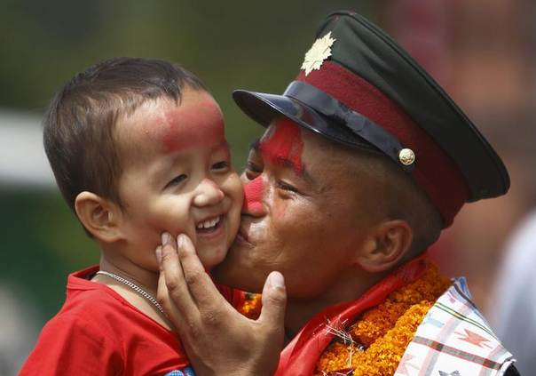 A former Maoist rebel kisses his son after being integrated as a lieutenant into the national army, as part of the peace deal, at Nepal Military Academy at Kharipati in Bhaktapur August 26, 2013 REUTERS/Navesh Chitrakar