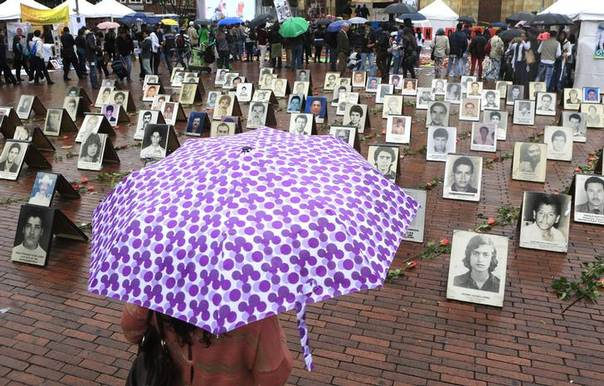 A woman holding an umbrella looks at portraits of missing people during an event observing International Week of the Disappeared, in Bogota May 27, 2014. REUTERS/Jose Miguel Gomez