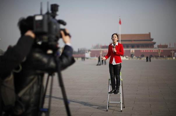 A journalist reports outside the Great Hall of the People at Tiananmen Square in Beijing March 5, 2013. REUTERS/Carlos Barria