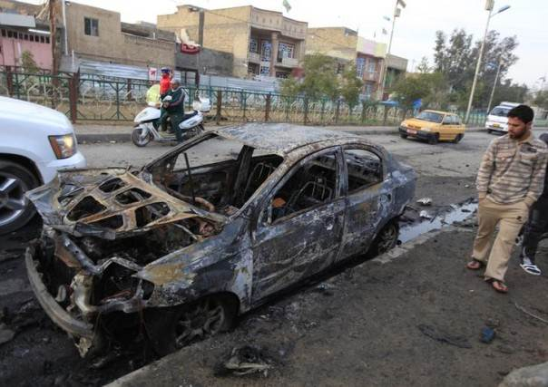 People gather at the site of a car bomb attack in Baghdad's Ghazaliya district, January 15, 2014. REUTERS/Ahmed Saad