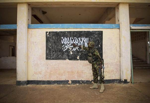 A soldier of the Kenyan Contingent serving the African Union Mission in Somalia (AMISOM) gestures at an al Shabaab flag painted on a wall at Kismayu airport, October 2, 2012.  REUTERS/African Union-United Nations Information Support Team/Stuart Price/Handout