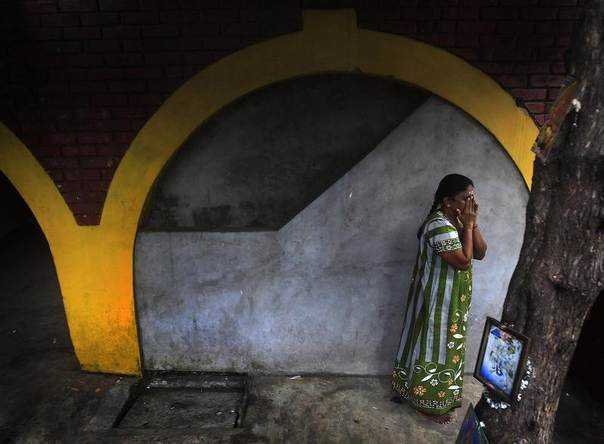 A Tamil woman prays at a small Hindu temple near her house before the start of her day in Colombo, Sri Lanka, January 29, 2014. REUTERS/Dinuka Liyanawatte