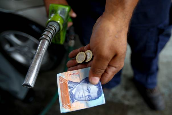 A worker shows money equivalent to about USD$0.60 (at official rate) after a driver paid that for more than 40 liters to fill his tank at a service station in Caracas, Venezuela, on August 7, 2014. REUTERS/Jorge Silva