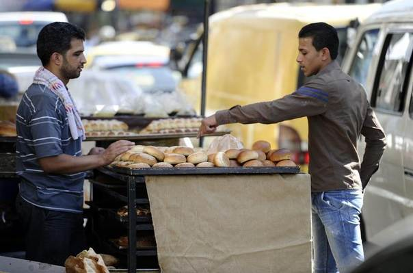 A man buys traditional bread before iftar, the breaking of fast meal, during the Muslim fasting month of Ramadan in Al-Medan district in Damascus, Syria, July 1, 2014. REUTERS/Omar Sanadiki