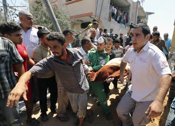 Palestinians carry the dead body of a man after being removed from under the rubble of a house, which witnesses said was destroyed by an Israeli air strike, in Beit Lahiya in the northern Gaza Strip, August 25, 2014. REUTERS/Mohammed Salem