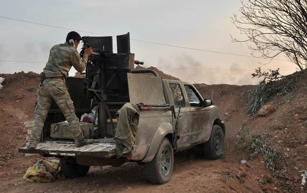 A Kurdish People's Protection Units (YPG) fighter fires his weapon towards forces from the al Qaeda-linked Islamic State in Iraq and the Levant (ISIL) in Al Rawiya village, Ras Al-Ain countryside, Syria, April 4, 2014, Picture taken April 4, 2014. REUTERS/Rodi Said