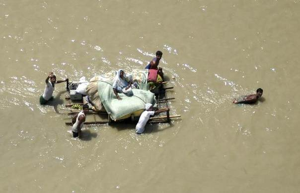 People salvage their belongings in a improvised boat from flood waters in east Nepal August 24, 2008. REUTERS/Nepal Army 11 Brigade/Handout