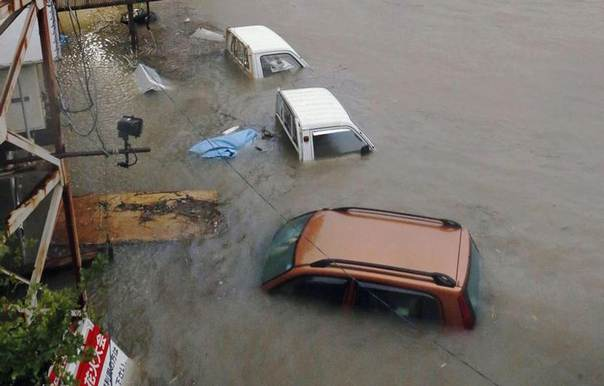Stranded cars are seen in floodwater caused by Typhoon Halong in Kochi, western Japan in this photo taken by Kyodo August 10, 2014. Typhoon Halong killed one person in Japan on Sunday and injured 33, media said, as authorities ordered 1.6 million people out of the path of the storm that battered the west of the country with heavy rain and wind. REUTERS/Kyodo
