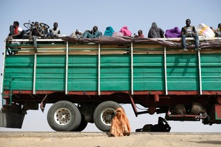 Refugees rest on, under and next to a truck in the Muna Garage area on the outskirts of Maiduguri, Nigeria