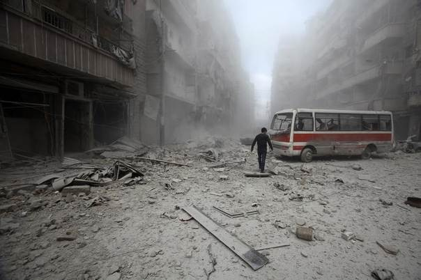 A man inspects the damage at a site hit by what activists said were barrel bombs dropped by forces loyal to Syria's President Bashar al-Assad in Aleppo's district of al-Sukari March 16, 2014. REUTERS/Ammar Abdullah