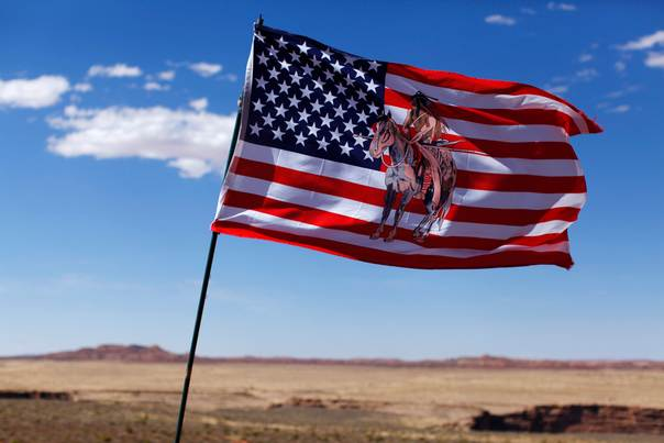 A U.S. flag with an image of an American Indian horse rider flies next to a roadside jewellery stand on the Navajo Reservation, by a remote section of the Grand Canyon near Little Colorado River, Arizona June 23, 2013. REUTERS/Mike Blake