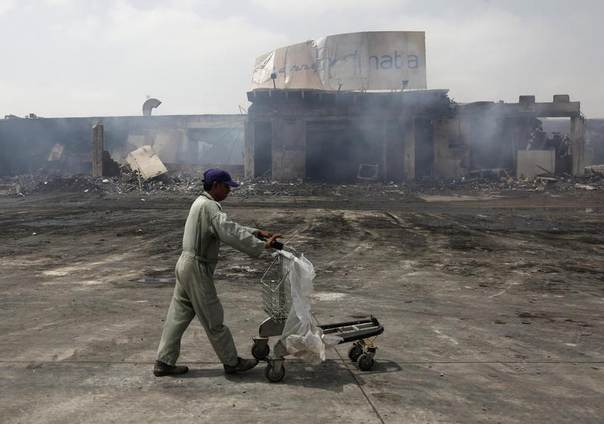 A man pushes a trolley past a damaged building on the tarmac of Jinnah International Airport, a day after Sunday's attack by Taliban militants, in Karachi June 10, 2014. REUTERS/Athar Hussain
