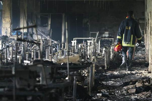 A firefighter inspects garment factory Tazreen Fashion factory in the Ashulia industrial belt of Dhaka, on the outskirts of Bangladesh's capital, after a fire killed 112 people, in the country's worst ever factory blaze. REUTERS/Andrew Biraj