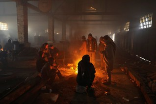Migrants warm themselves by the fire inside a derelict customs warehouse in Belgrade