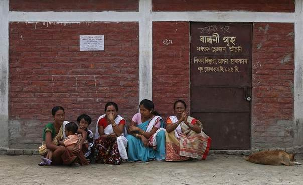 Women wait outside a polling station for their relatives after casting their vote in Majuli in India's Assam state, April 7, 2014. REUTERS/Adnan Abidi