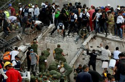 Soldiers, rescuers and civilians work at a collapsed building after an earthquake in Mexico City