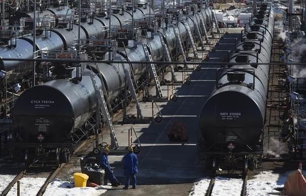 Irving Oil workers inspect rail cars carrying crude oil at a terminal in Saint John, New Brunswick, Canada, March 9, 2014. REUTERS/Devaan Ingraham