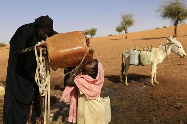 A girl is helped by her sister as she drinks water in Mellit town in North Darfur March 24, 2014. REUTERS/Mohamed Nureldin Abdallah