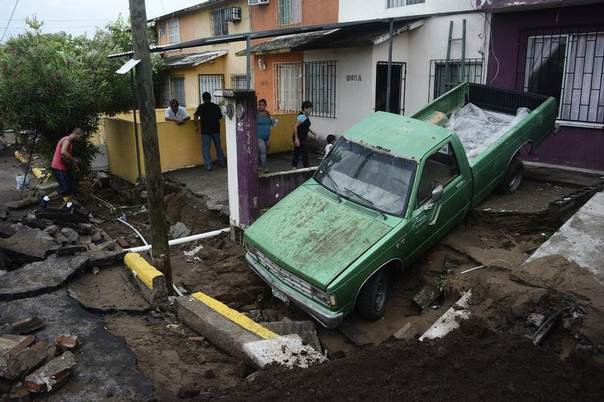 A pickup truck is seen after a street was damaged due to heavy rains, as residents look at damages in Veracruz September 2, 2014. REUTERS/Jonatan Rosas